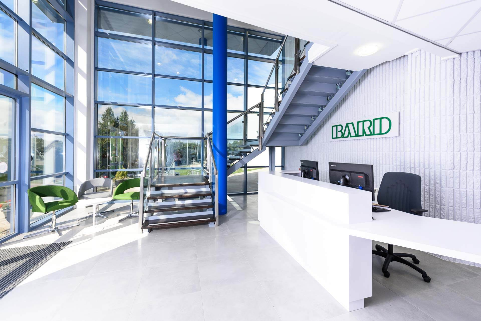 Double height entrance atrium with steel and glass staircase with feature blue column, green and grey tub chairs and white laminate disabled accessible reception desk on grey large format porcelain tiles.