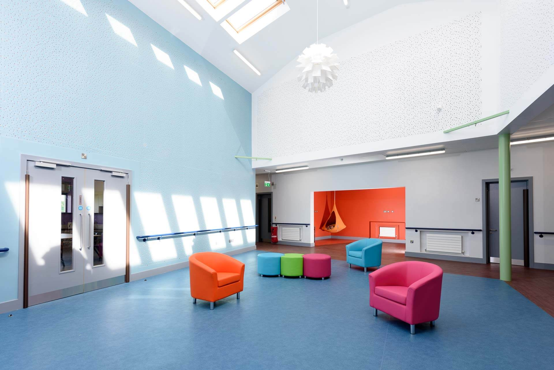 Central activity area with orange safe area off main single storey circulation area with rooflights, pendant light fittings and light blue rigitone acoustic wall forming central space consisting of orange, pink, green and blue stools and tub chairs.