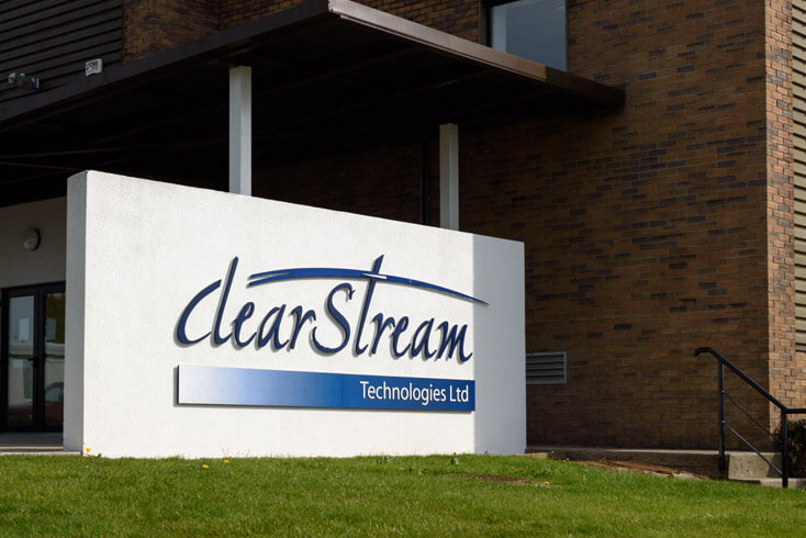 Signage wall with Clearstream logo pin mounted to wall with brown brick wall in background.