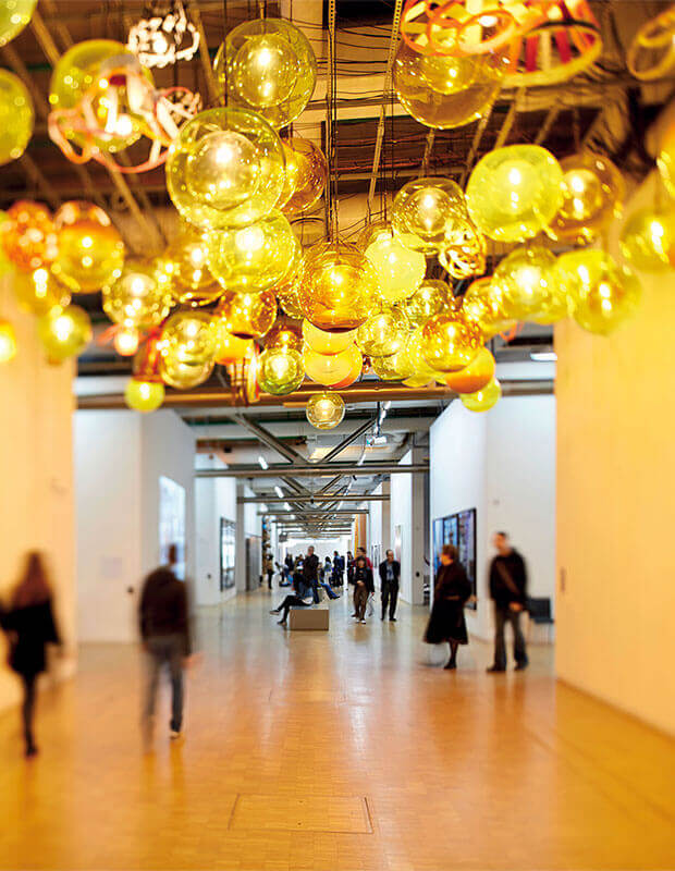 Circulation route in Pompidou centre with yellow feature hanging from ceiling and people walking underneath.