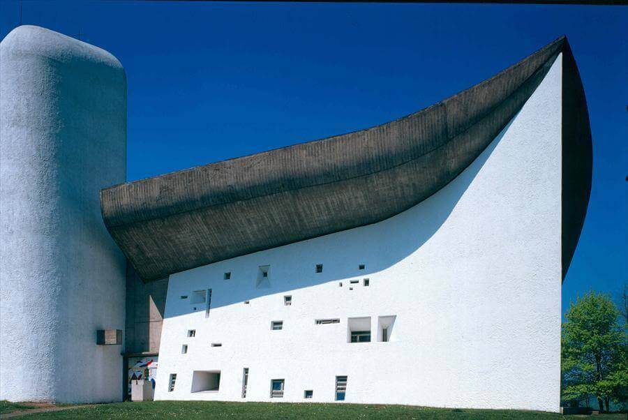 Curved concrete roof and white painted bell tower at Chapelle Notre Dame Du Haut (Ronchamp) by Le Corbusier.