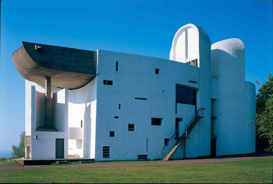 White bell towers and small window openings in large white walls with concrete roof and external staircase Chapelle Notre Dame Du Haut (Ronchamp) by Le Corbusier.