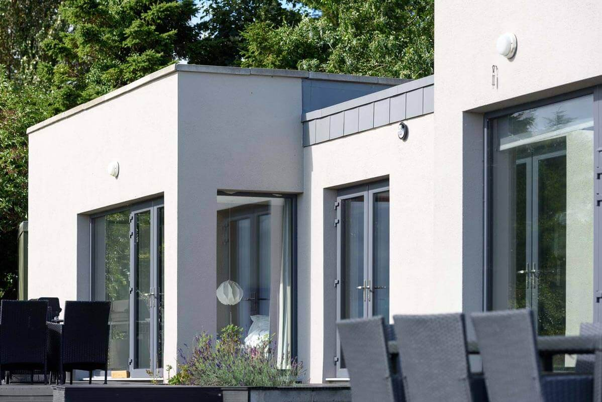 Flat roofed passive house with concrete and metal parapet details and triple glazed grey aluminium windows with grey wicker seating on external terrace.
