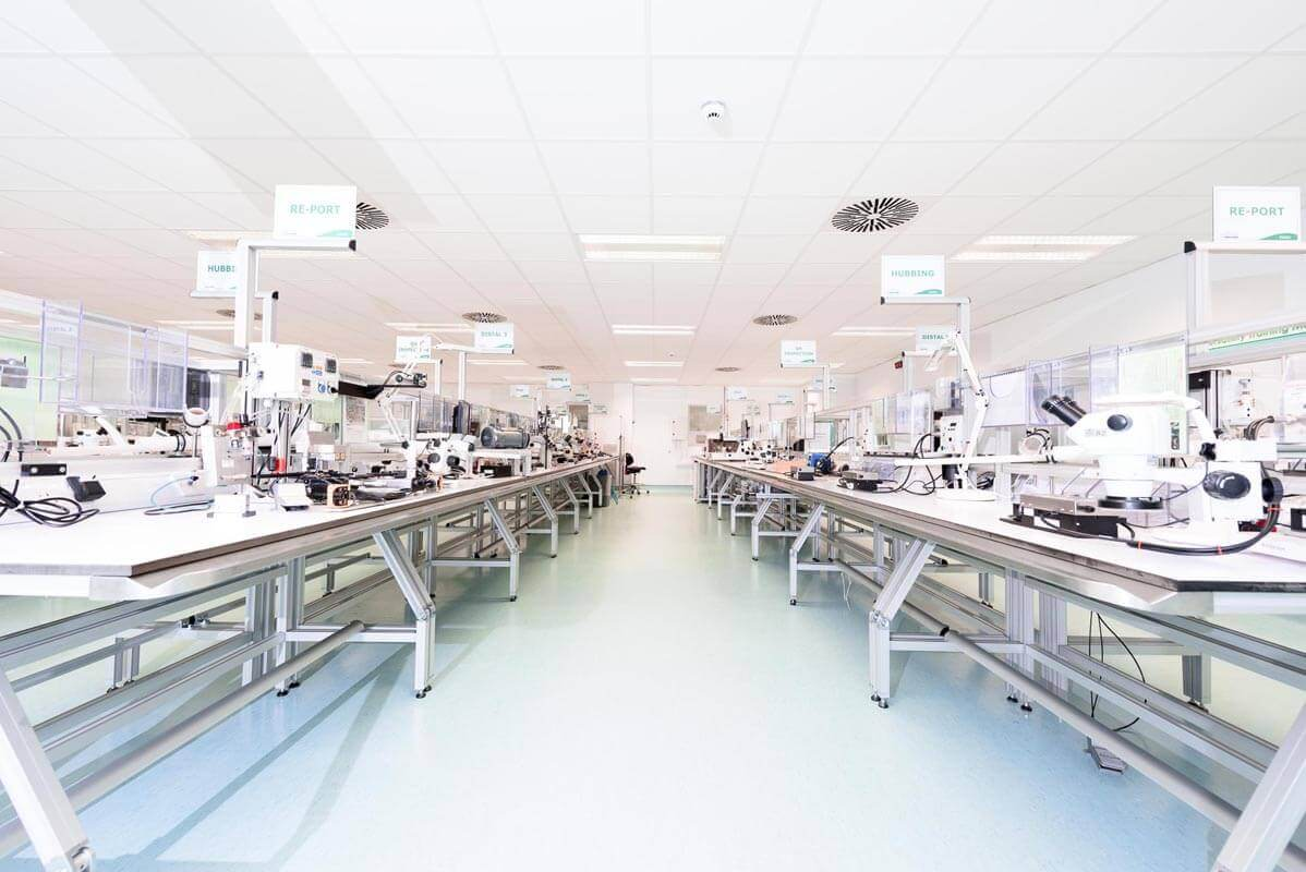 Pharma- medical device cleanroom with work benches and equipment making up production lines for product assembly with MF suspended ceiling and vinyl flooring.