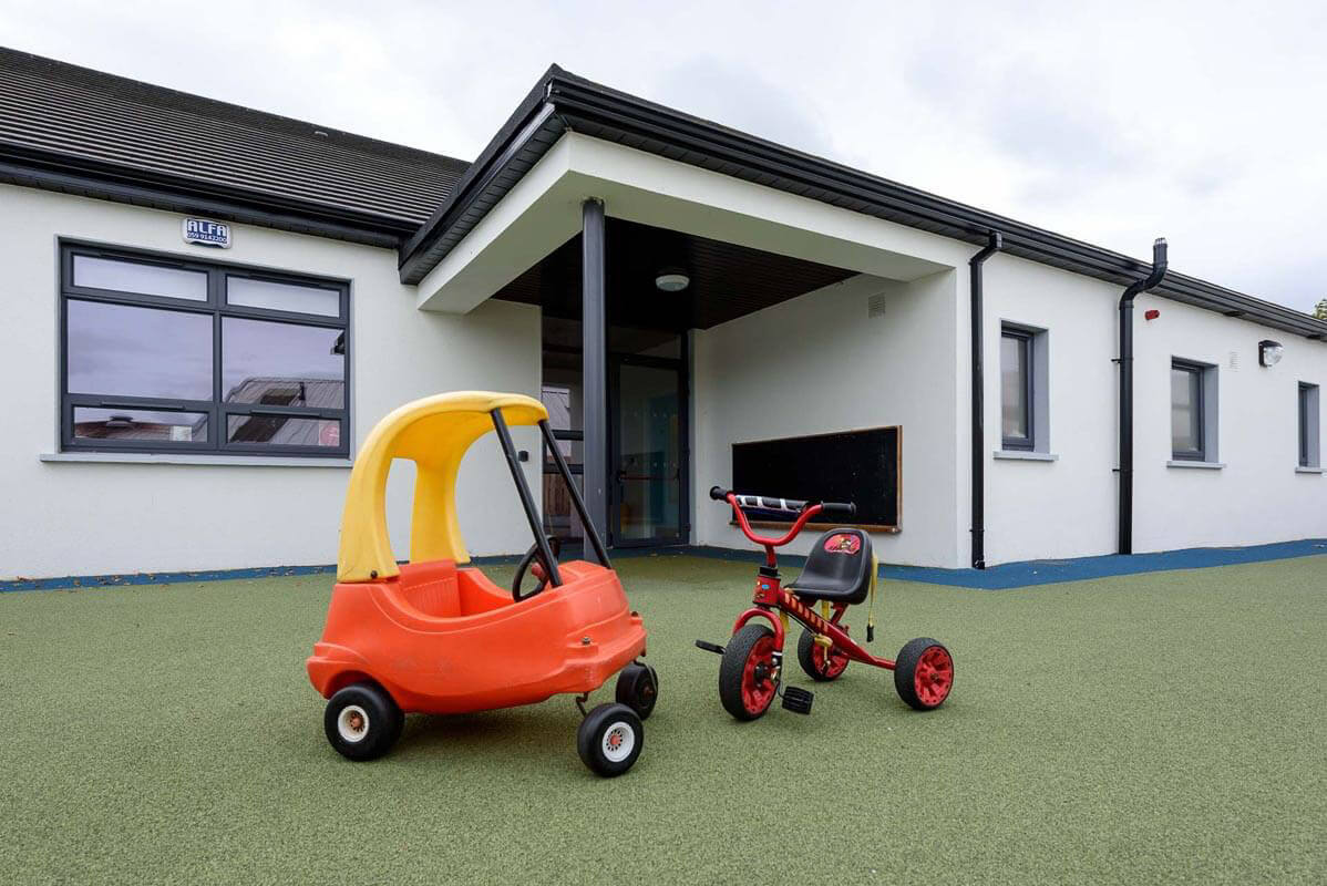 Covered external area off mainstream classroom of pre-school autistic spectrum disorder facility with fully enclosed play area with yellow and orange toys on green astro turf.