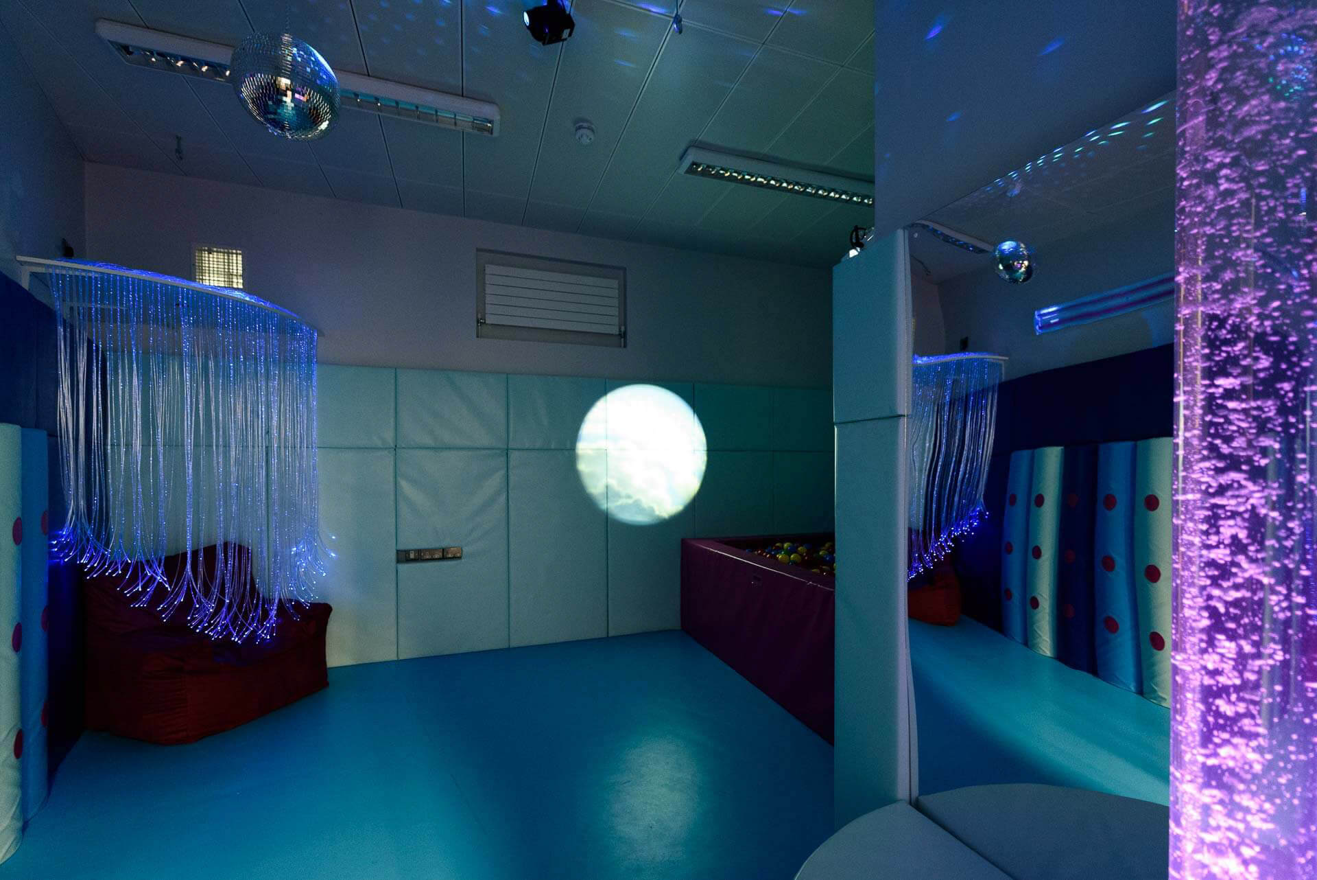 Multi-sensory room with multi coloured wall padding, led lighting, projector and pink coloured lava lamp with wall mirrors in the background.