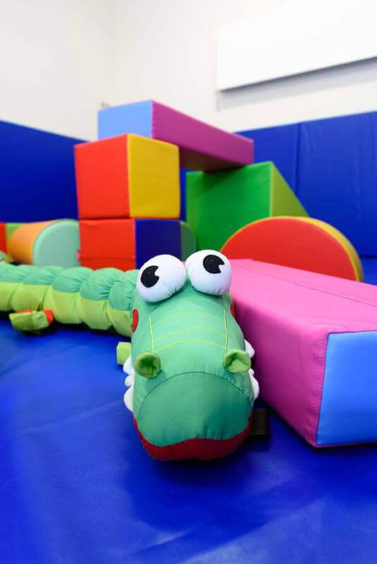 Soft play area in multi-sensory room with blue padded walls and brightly colours building blocks with green snake.