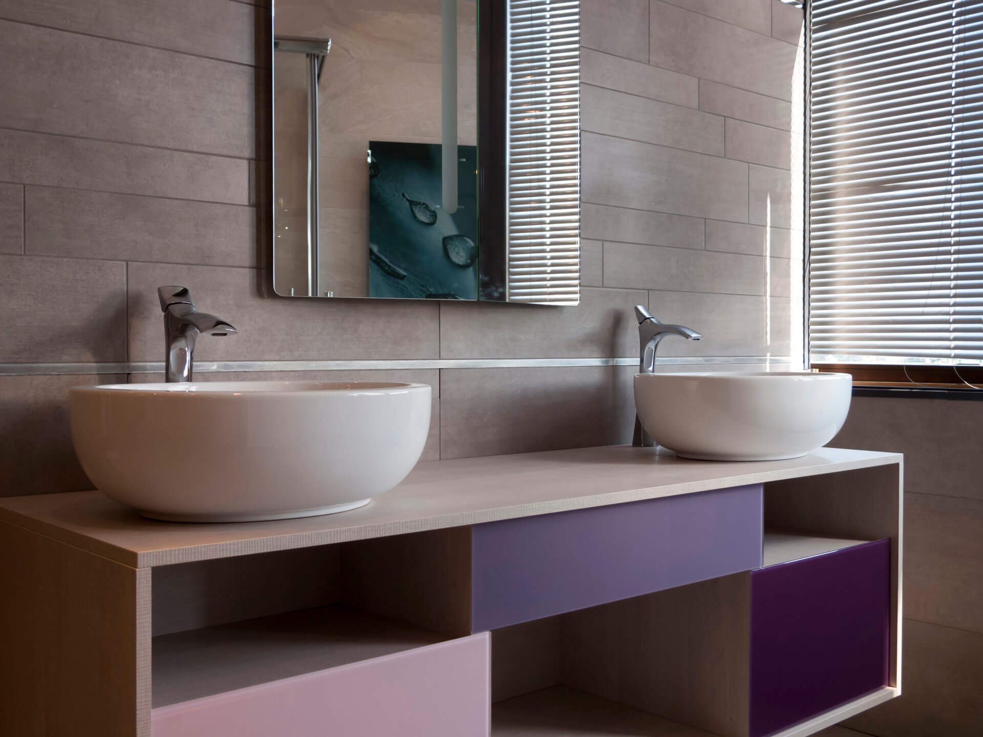 Contemporary bathroom design with two bowl wash hand basins on top of floating storage unit with a selection of open and closed storage units in accent colours.