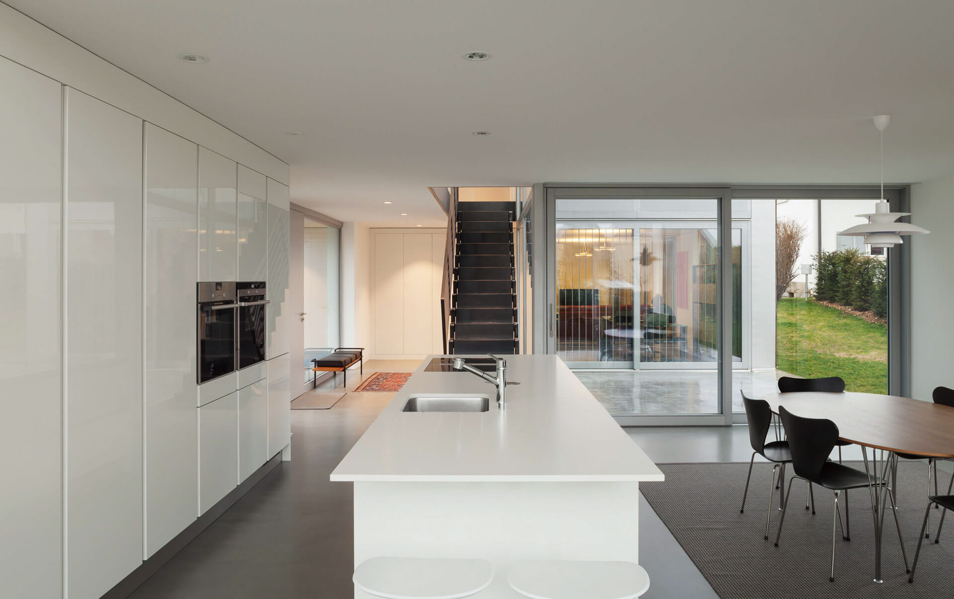 Bespoke white kitchen with island unit in open plan living area of passive house.