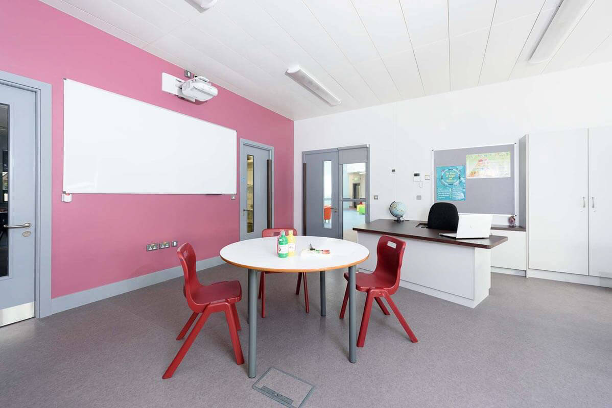 Mainstream classroom with pink accent wall and bespoke teachers desk with red chairs and circular white tables on grey acoustic flooring with white perforated acoustic metal ceiling.