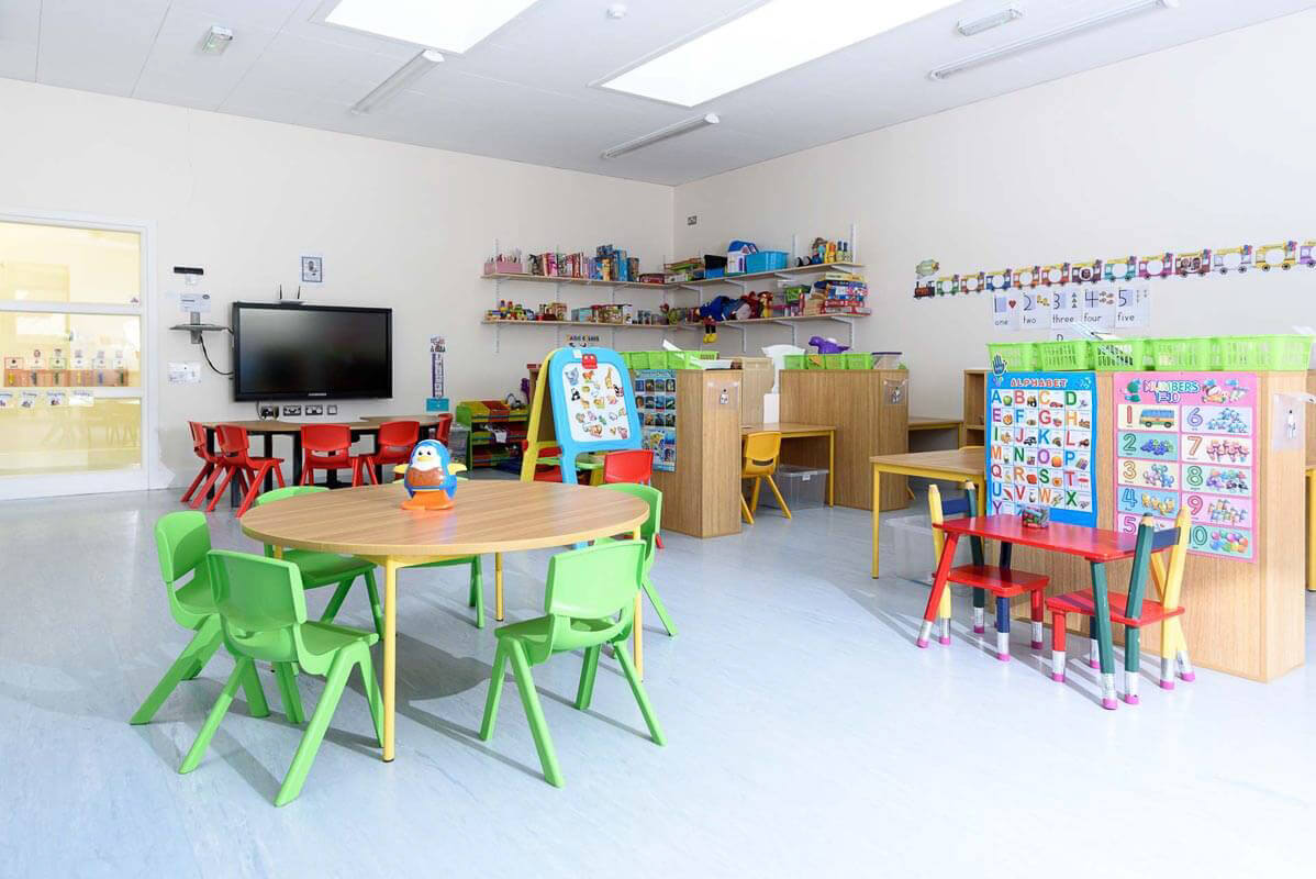 Pre-school classroom with green chairs and circular timber veneer tables on a light blue vinyl floor.
