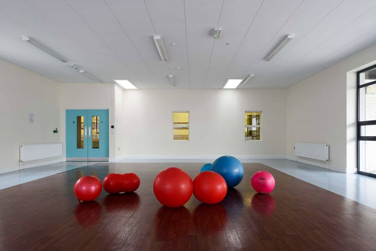 Main central activity area with duck egg blue double doors and large and small blue, red and pink exercise balls on timber effect acoustic vinyl flooring.