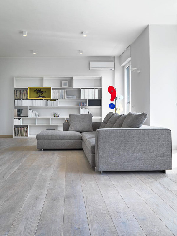Well lit modern open plan living area with white walls and contrasting grey sofa and timber flooring.