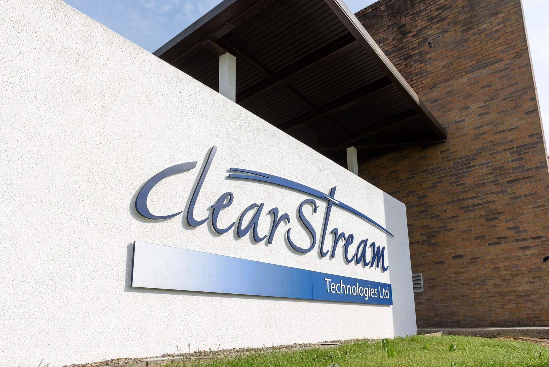 White signage wall with Clearstream logo pin mounted onto wall with brown brick façade and metal canopy.