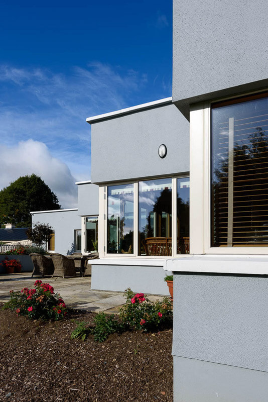 Flat roof with parapet detail over series of white painted aluclad corner windows.