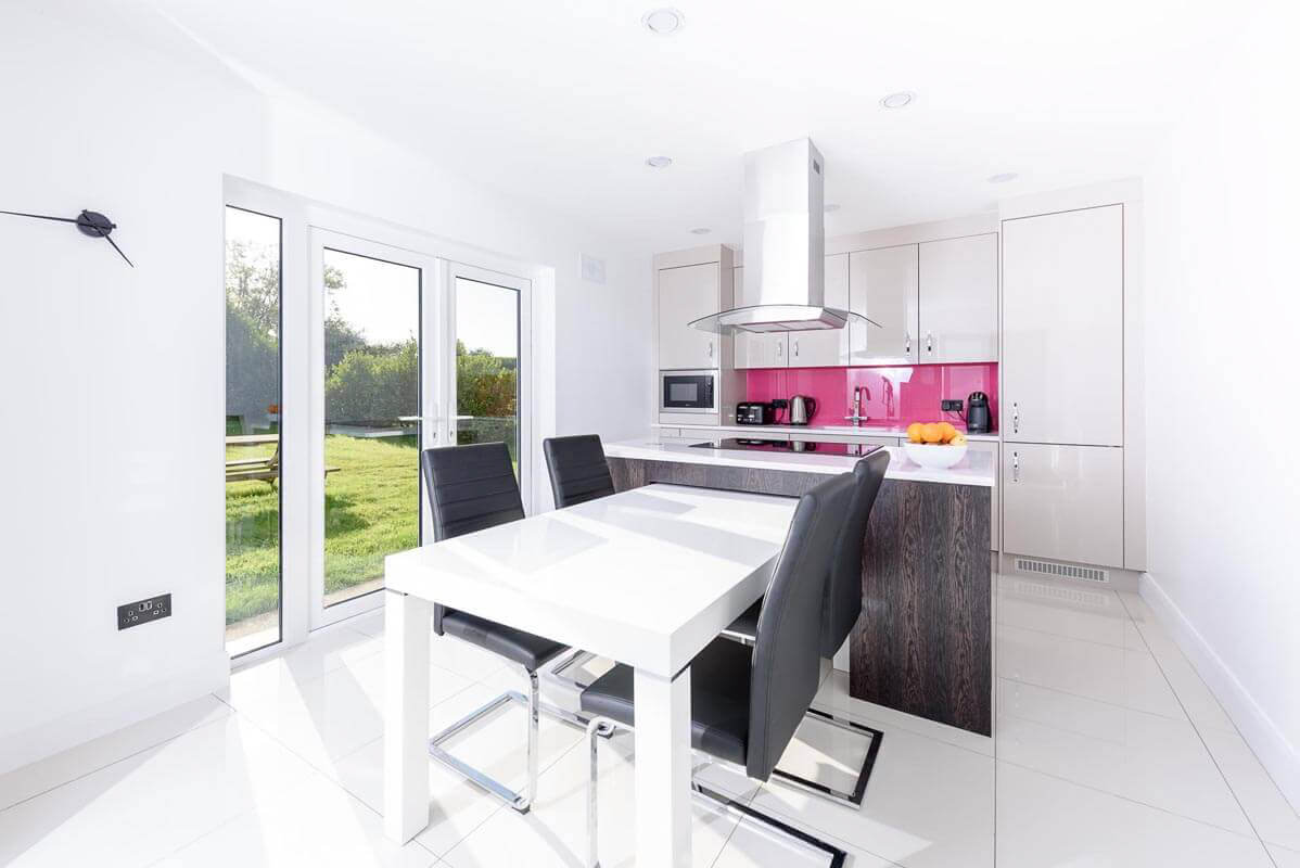 Contemporary kitchen design with white table, island unit and pink splash back.