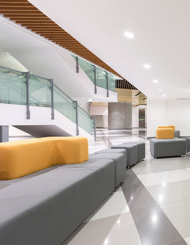 Double height atrium reception area with grey and yellow seating and staircases.