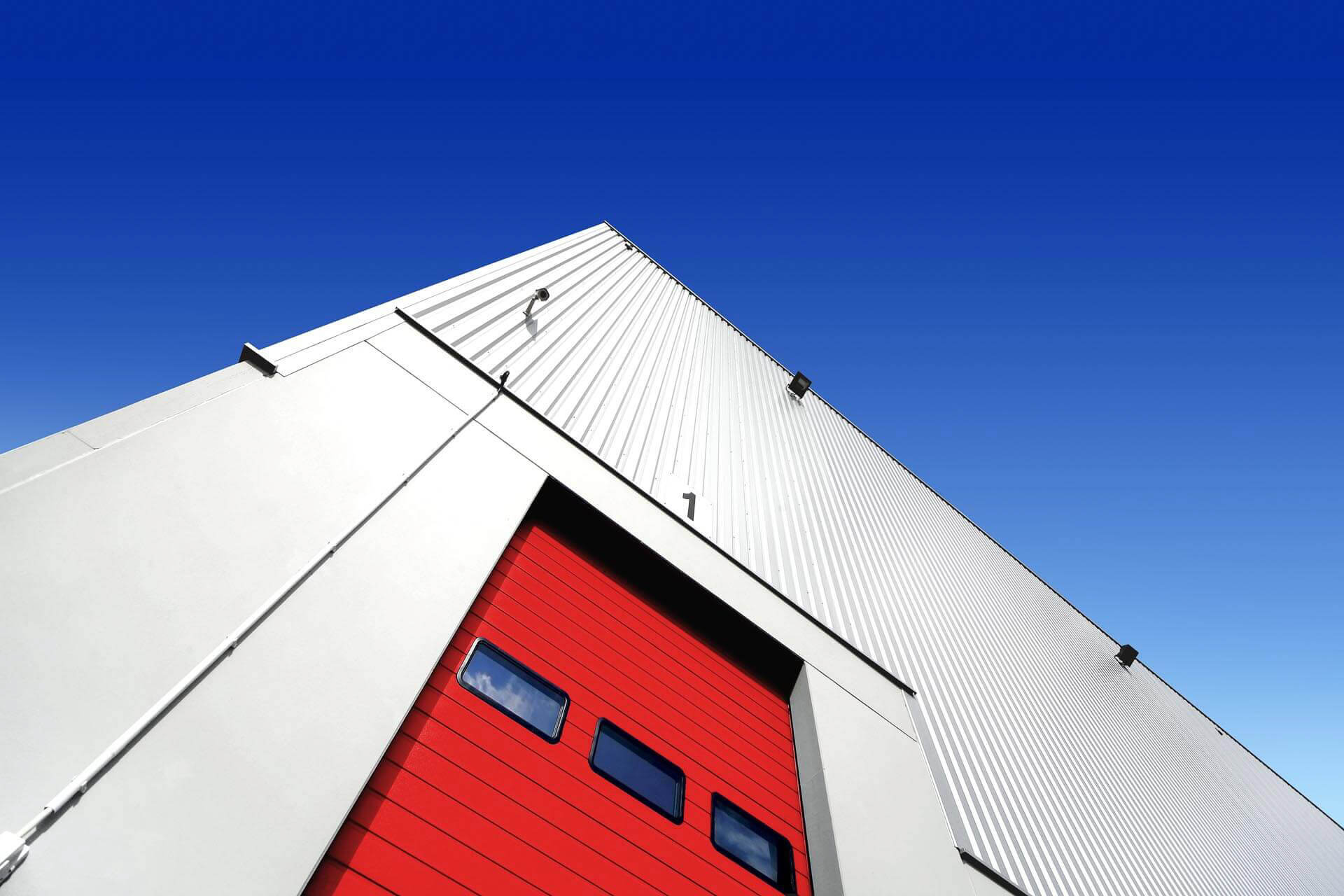 Red goods in folding entrance door with glazing and grey architectural metal cladding system and blue sky line.