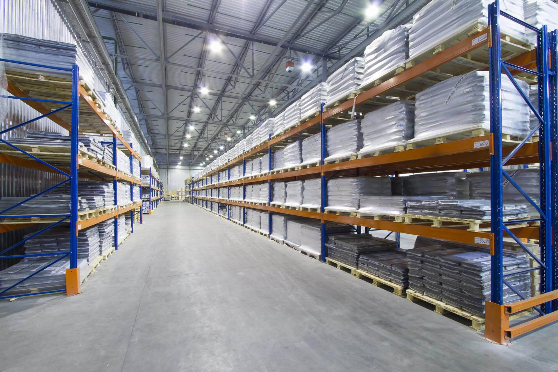 Blue warehouse double height raking system with pallette storage and large aisle width with high bay light fittings on concrete floor.