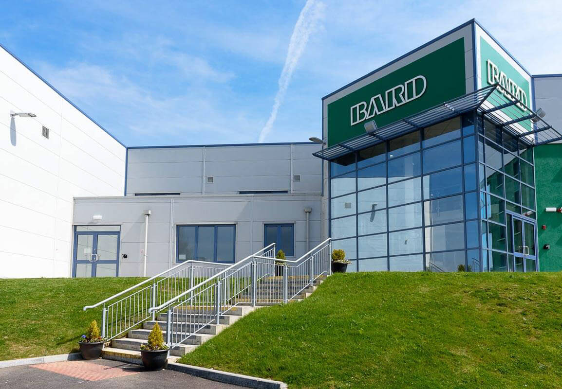 External steps to medical device factory with BARD signage over glazed atrium entrance area.