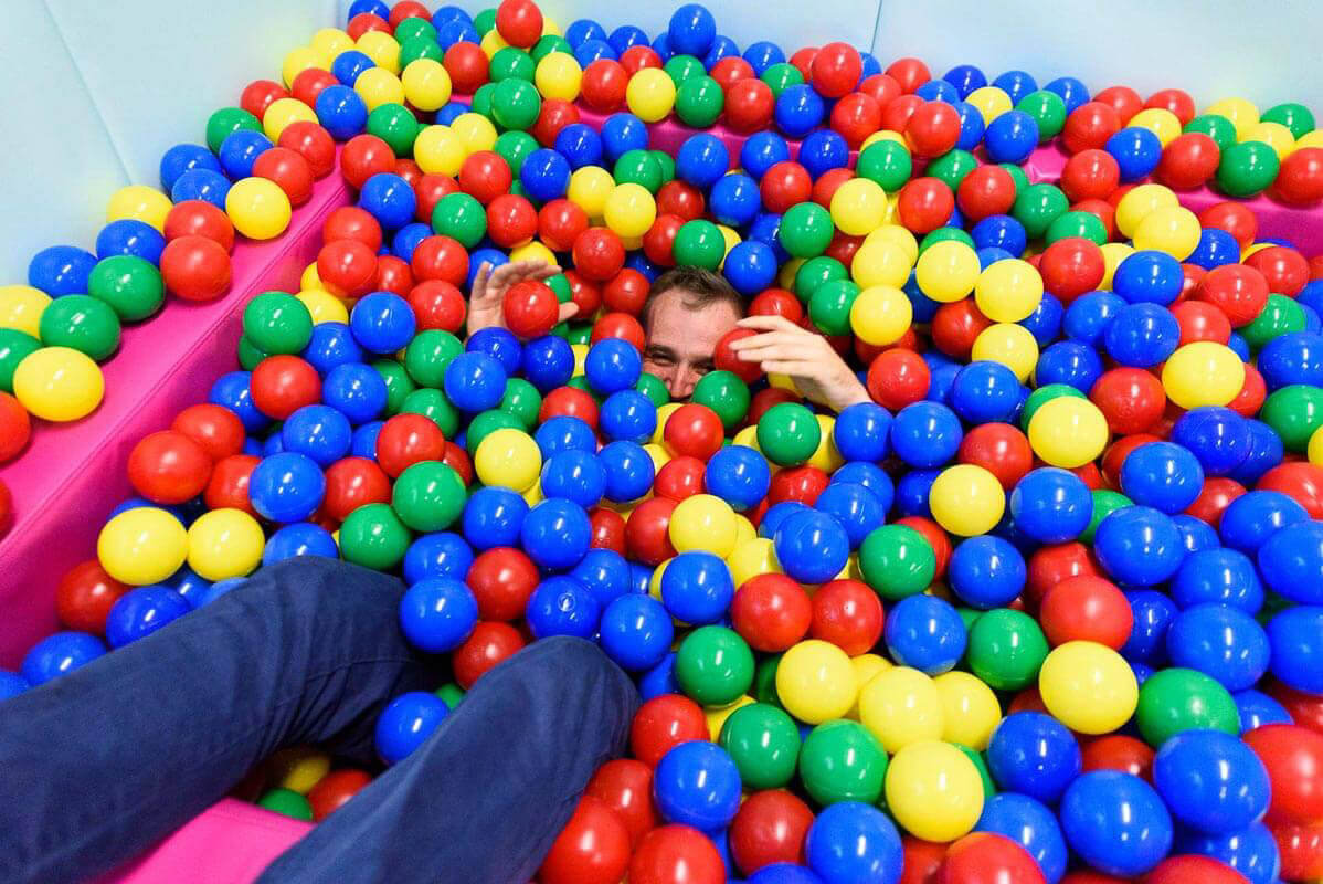 Student partially hidden in pink ball pit with red, yellow, blue and green balls.