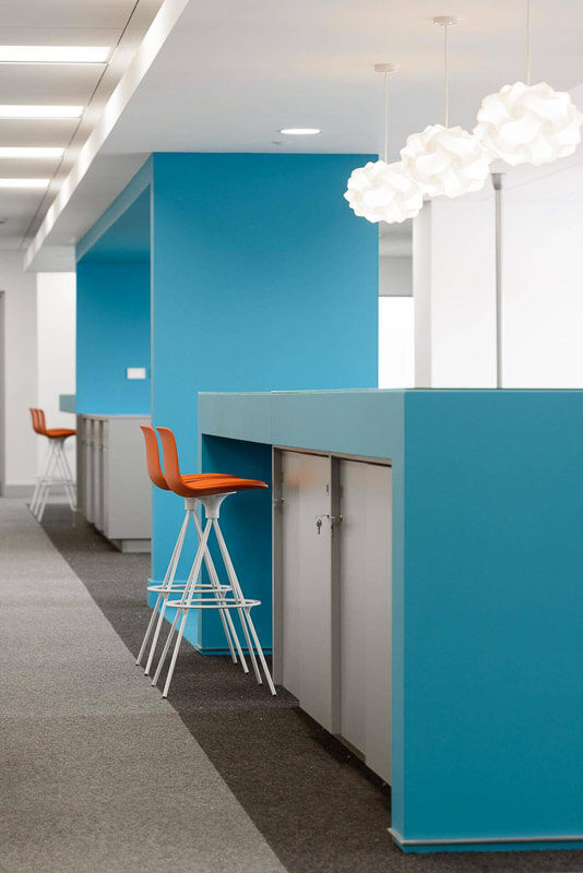 Blue feature walls in open plan office area forming informal meeting and storage areas with three feature pendants hanging from plastered ceiling.