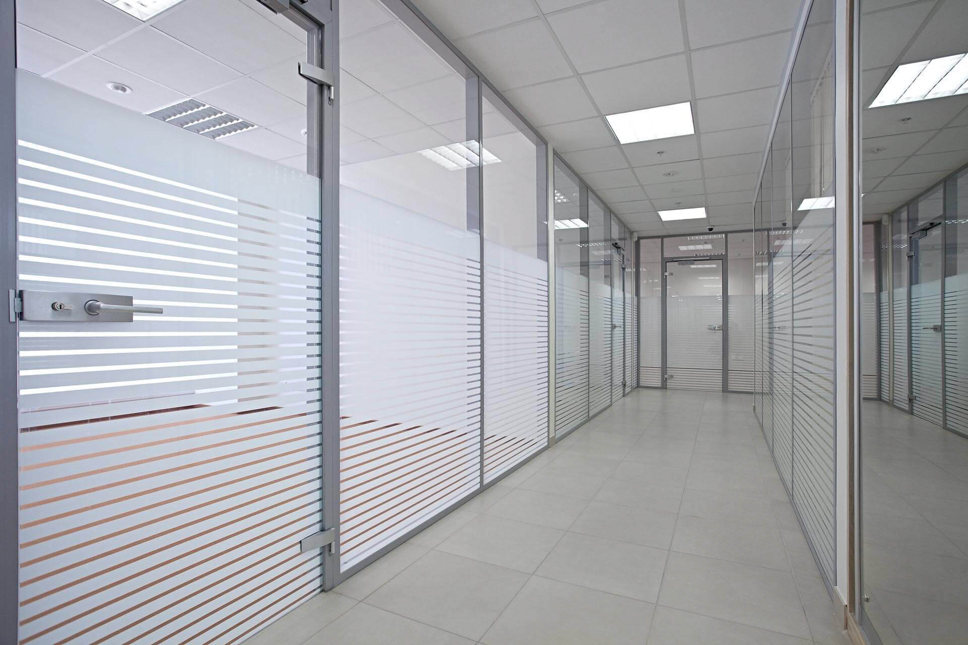 Office corridor with glazed partitions with stripped manifestations for privacy screens.