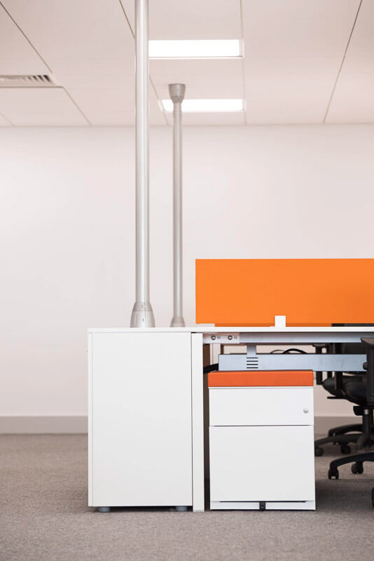 White office desk with white gable storage, orange divider and grey service pole with data and electrical services connected through acoustically rated MF grid ceiling.