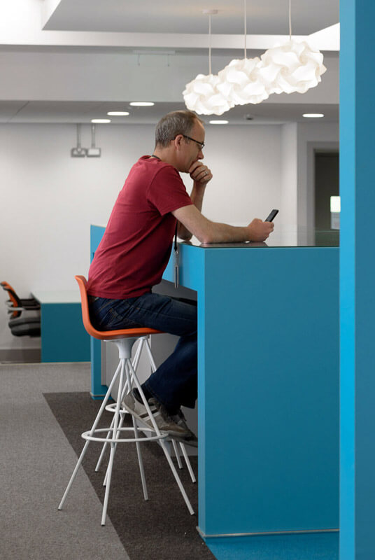 Architect on phone sitting at blue hot desk in open plan meeting area with pendant light fittings.
