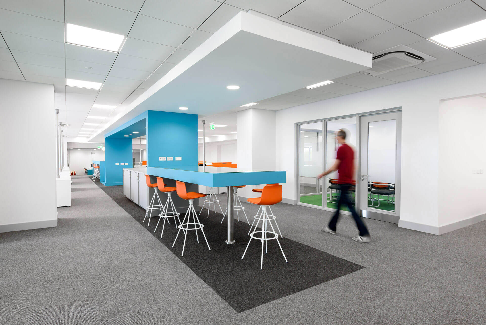 Open plan office area with blue snake feature and orange high stools forming informal meeting area, printing stations and storage area.