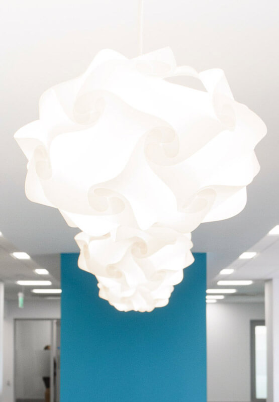 Feature white light shade hanging from feature white plasterboard ceiling with blue accent wall.