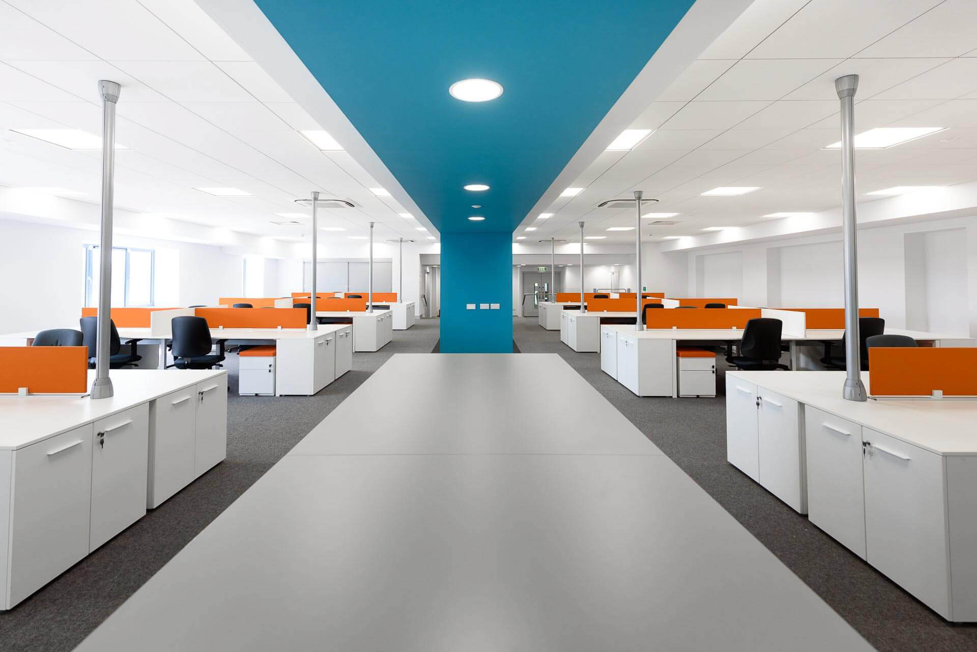 Open plan office area with blue snake feature forming print station and stationary area with white office desks, orange privacy screens and grey office chairs.
