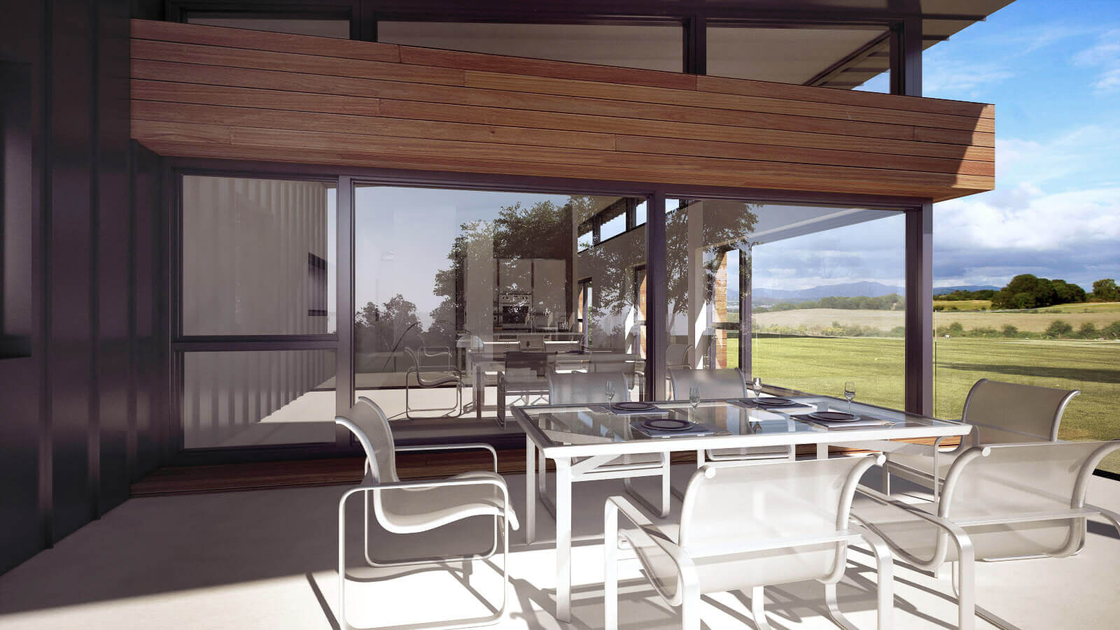 External raised terrace area with modern dining table and chairs overlooking the countryside and internal open plan living areas.