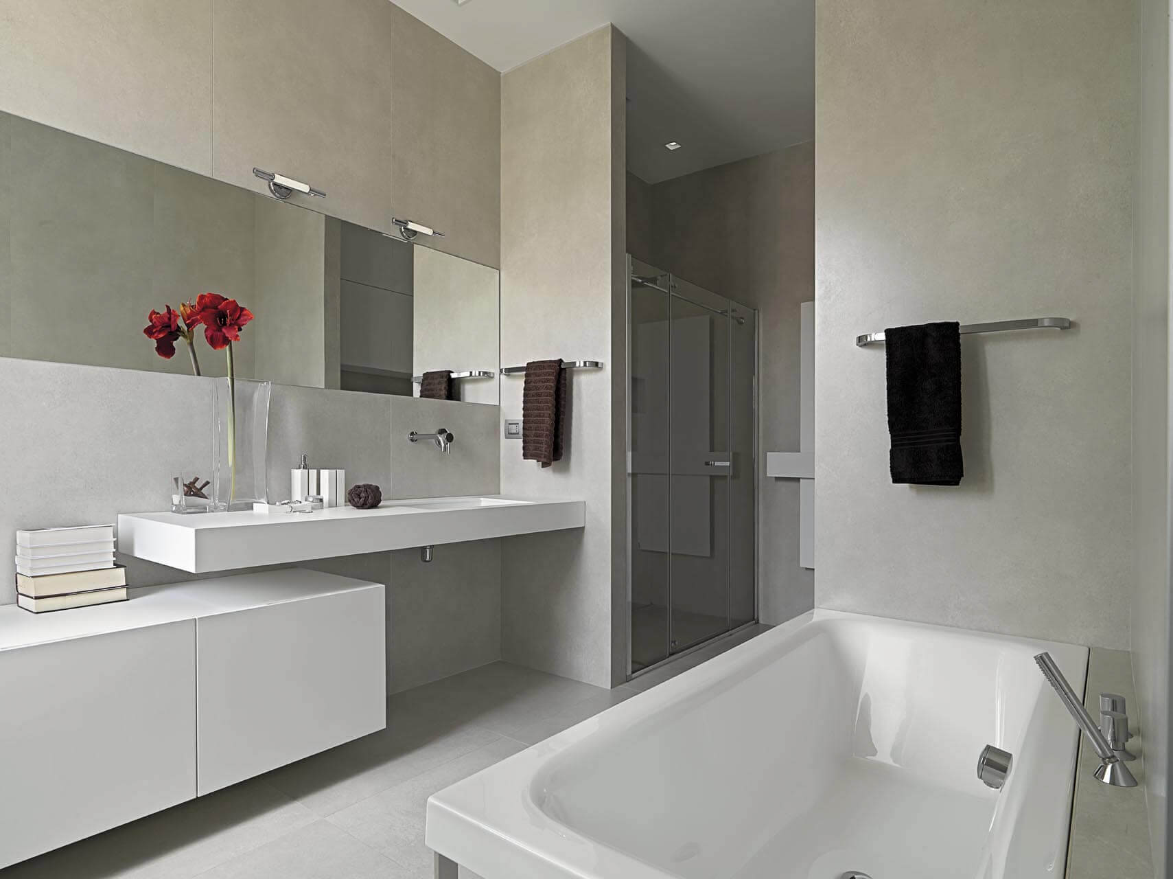 Contemporary family bathroom with white sanitary ware, floating shelves, grey walls and horizontal mirror.