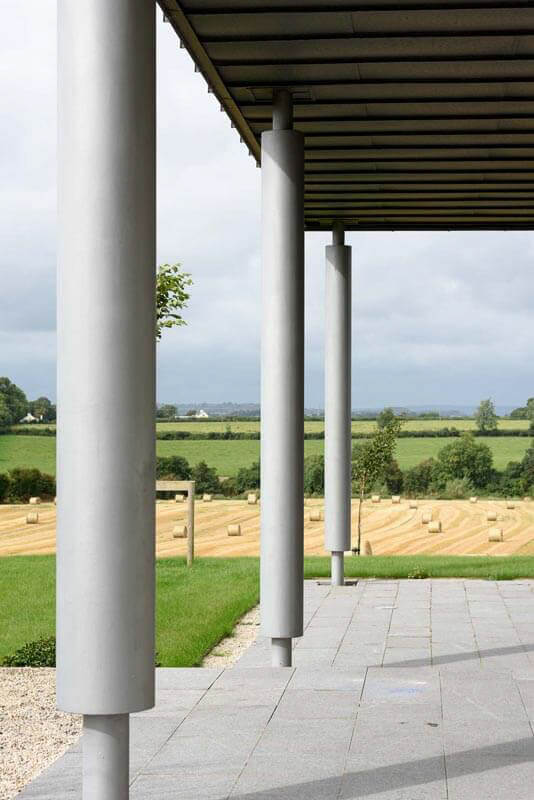 Underside of standing seam zinc canopy supported by powder coated columns with views towards the countryside.