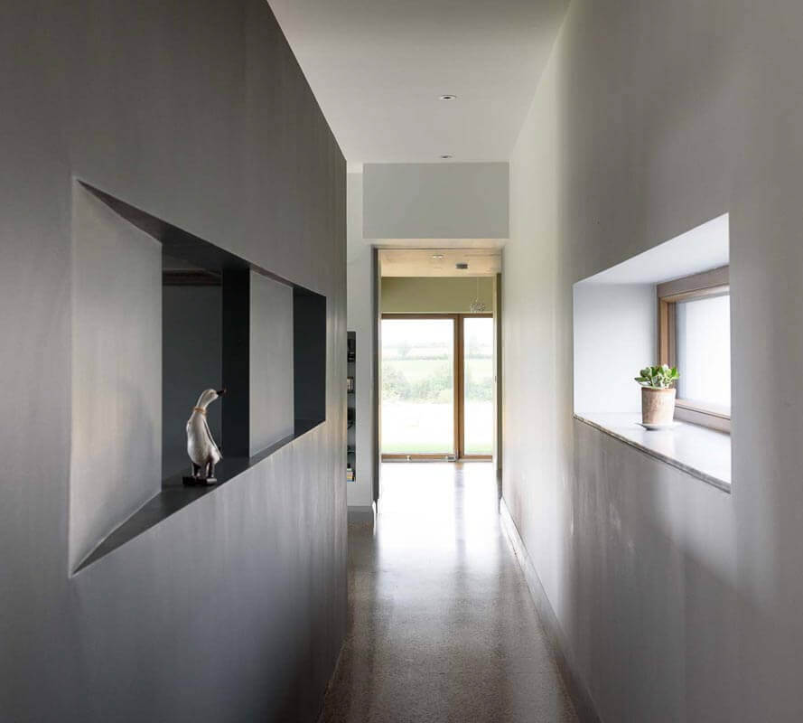 Circulation route in passive house framed by grey free standing bespoke kitchen and triple glazed alucald horizontal window.