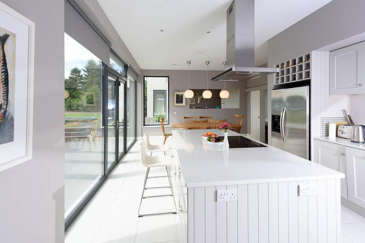 Bespoke architecturally designed light grey kitchen with large island unit and white leather high stools