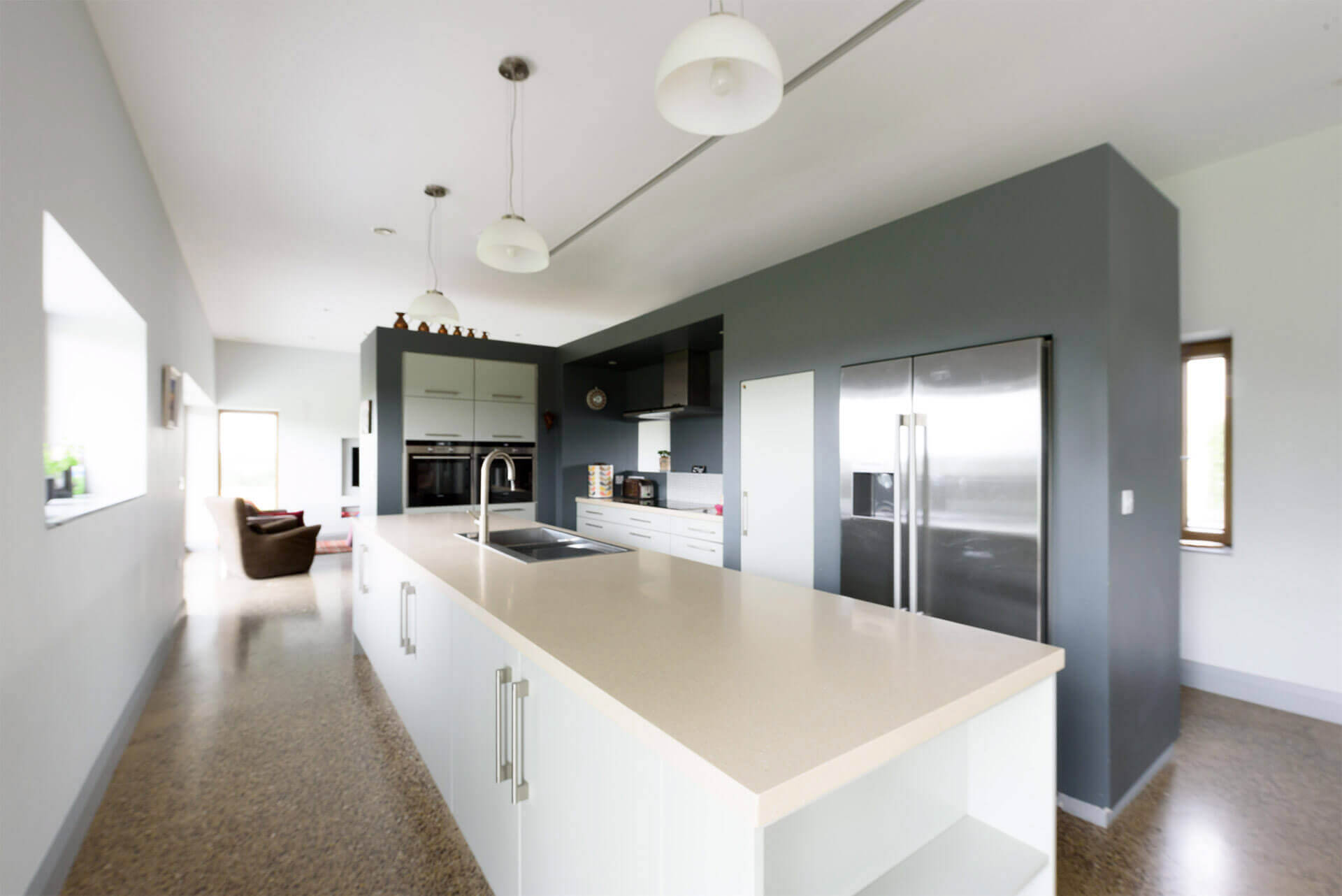 Bespoke kitchen with grey wall and white island units and polished concrete floor.