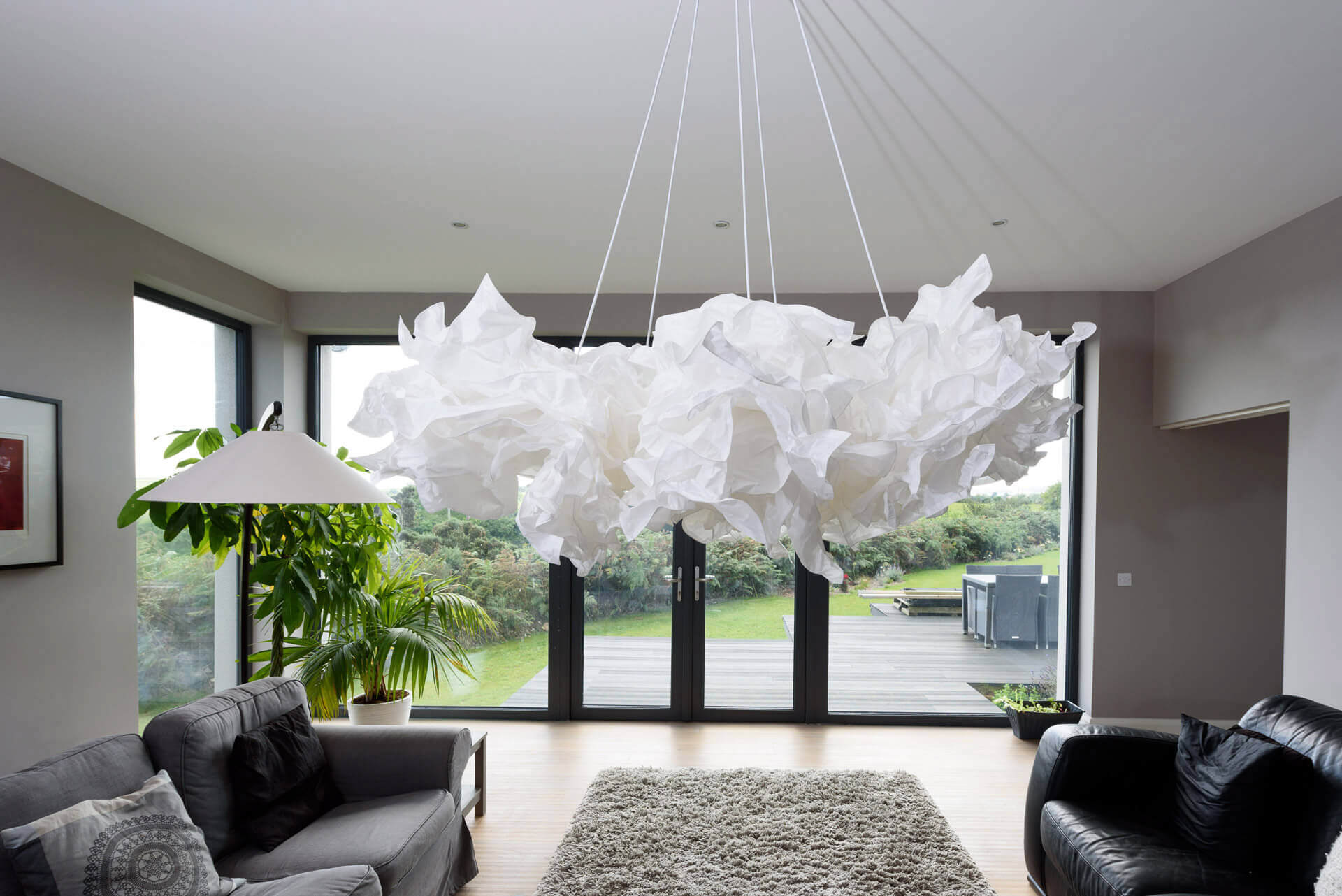 "Five Ikea ""cloud"" pendant light fitting grouped together to create a dramatic white centre piece contrasting against the grey walls and timber flooring."