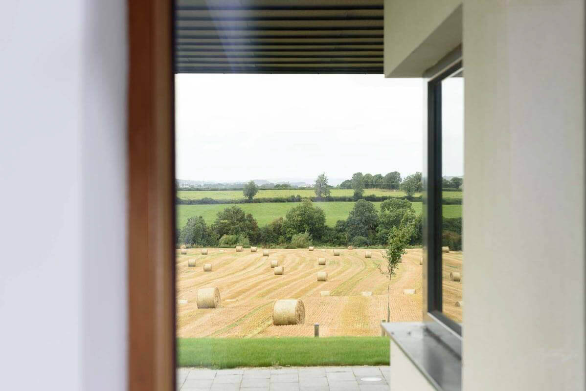 Window view of underside of zinc canopy, outdoor terrace and bales of hay in the distant field.