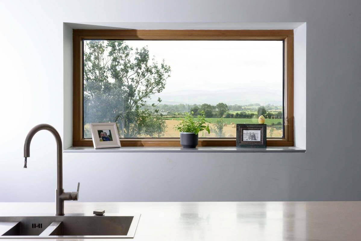 Bespoke kitchen island unit in passive house with view of countryside framed by the triple glazed aluclad window.