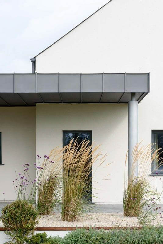 Zinc brise soleil supported off zinc column with painted rendered gable and landscaping.