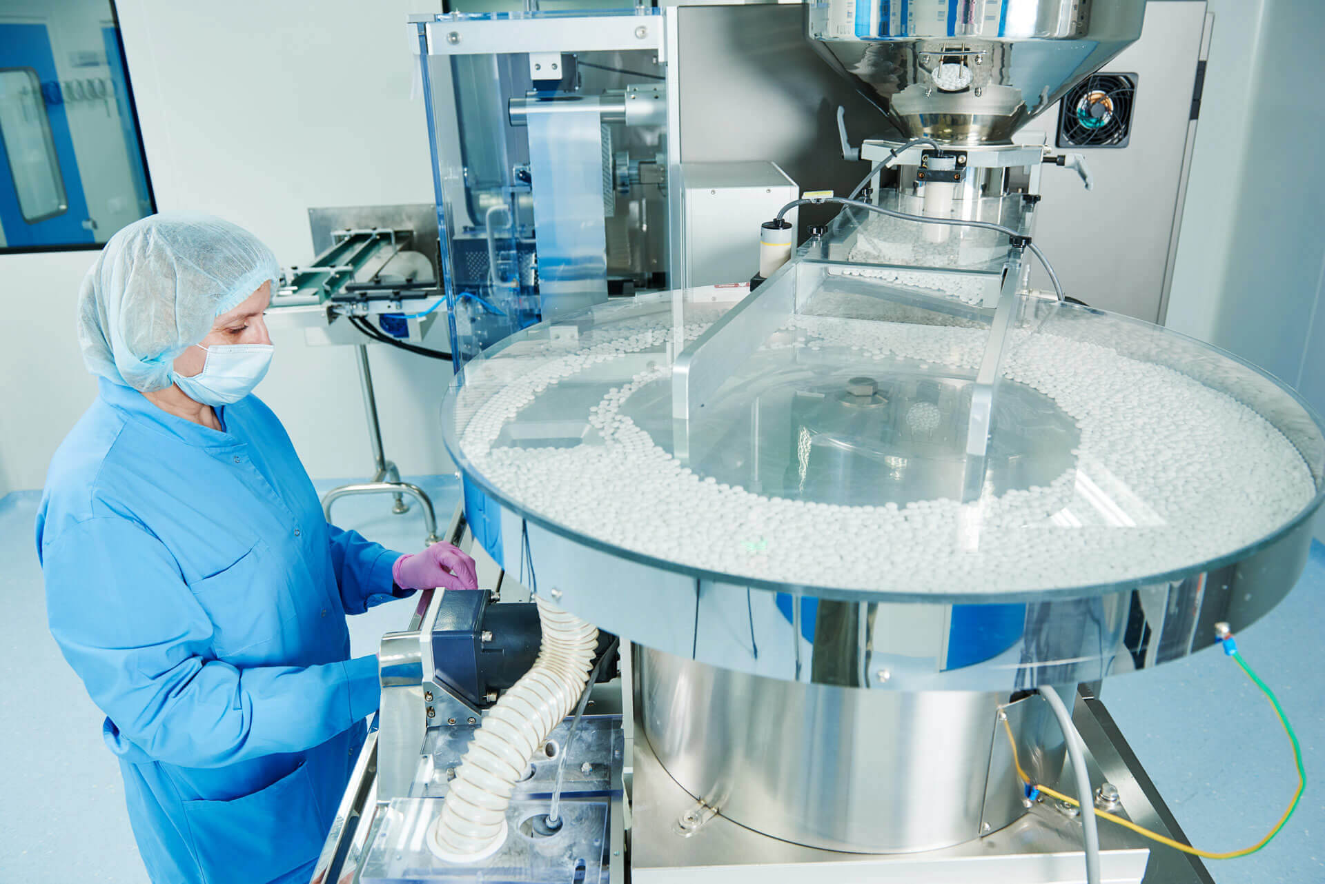 Person in blue gown working at pharmaceutical equipment in cleanroom.