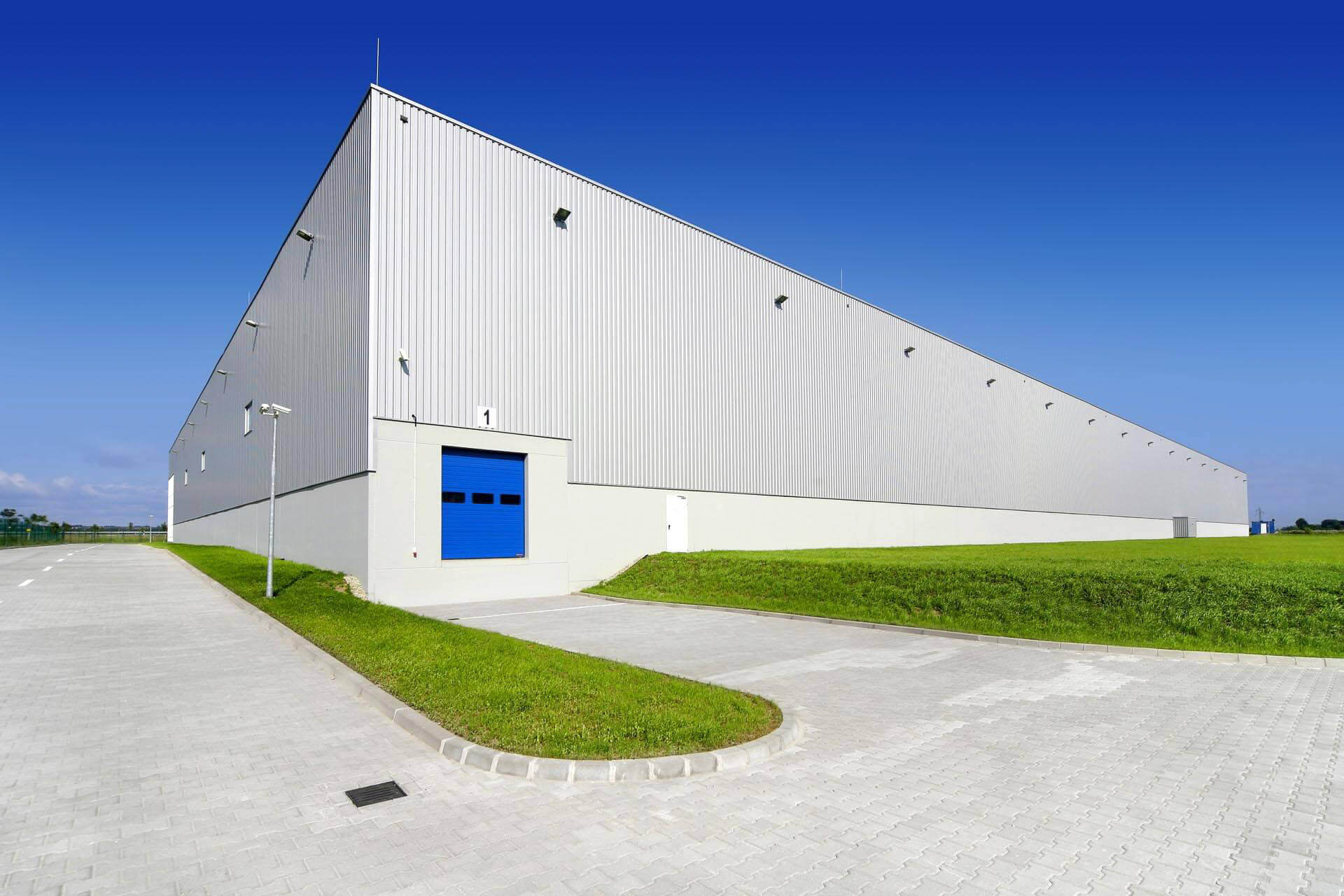 Grey wall cladding to factory with blue goods in door and concrete access roads.