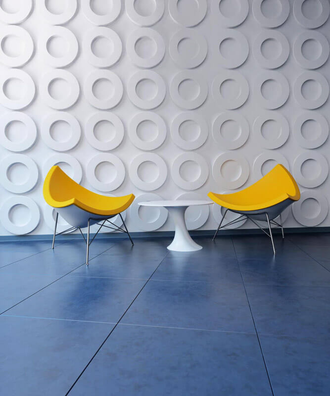 Textured feature wall consisting of projecting circle design with yellow tub chairs and small white coffee table.