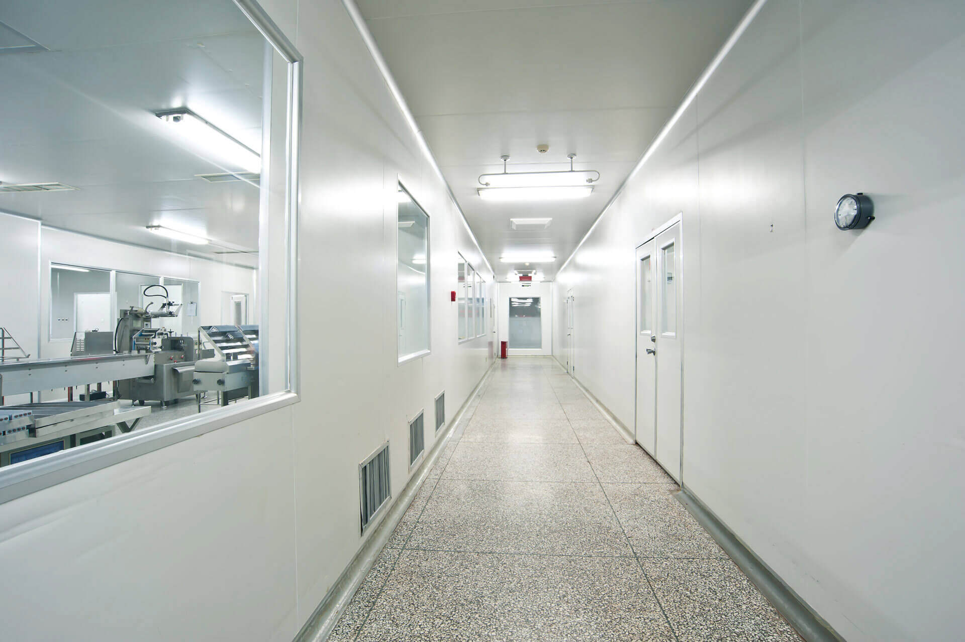 Corridor with viewing panels looking into pharmaceutical equipment in cleanroom.