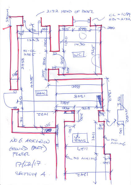 Freehand dimensioned survey of part of a commercial property in blue and red pen.